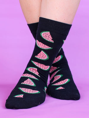 A close-up of an individual wearing the black organic kind socks with a pink watermelon print standing in front of a bright pink backdrop.