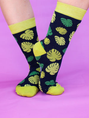 Green monstera leaf socks with lime green trim worn in front of a pale pink backdrop