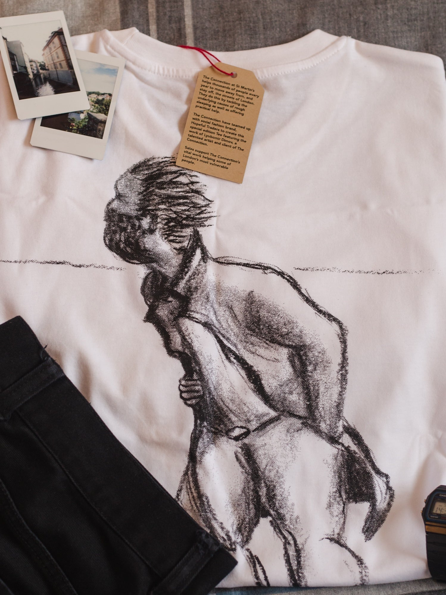 The organic 'footprints' tee folded so the drawn design of a figure walking in the cold on the back is clearly visible. The t-shirt is surrounded by  folded jeans, a casio watch and polaroid photos.