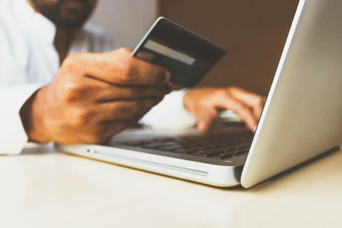 Hand holding credit card to purchase product online on a laptop computer