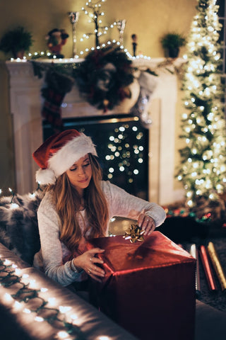Girl wearing santa hat opening a gift for Christmas