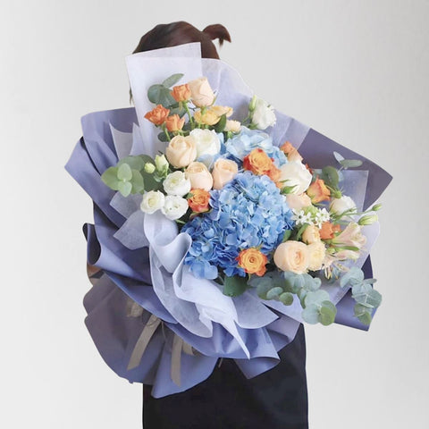 A bouquet of blue hydrangeas, orange roses and white roses