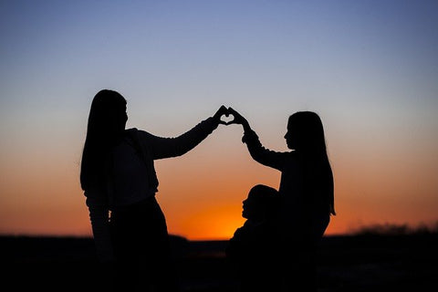 Silhouettes of two girls forming a heart and a girl sitting down