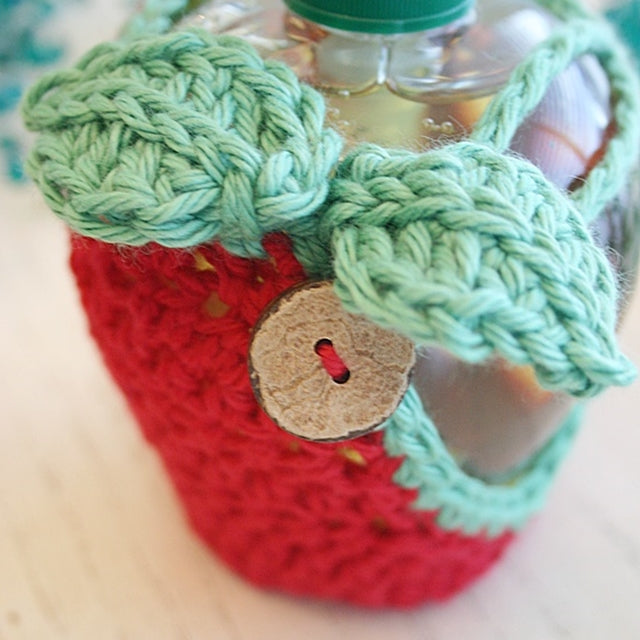 Red apple cozy for apple shaped soap dispenser with wooden button, crocheted by Susan Carlson of Felted Button | Colorful Crochet Patterns