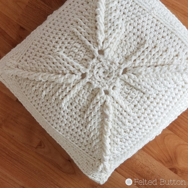 White textured crochet pillow cover on wood floor, free pattern using Asanas Square by Susan Carlson of Felted Button colorful crochet patterns