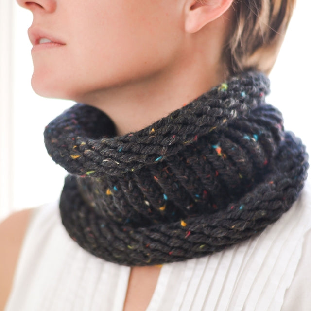 Knit black cowl with rainbow speckles on pretty girl, by Susan Carlson of Felted Button | Colorful Crochet Patterns