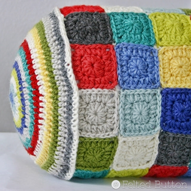 Bolster crochet pillow iwth circular stripes on ends and small granny squares, Susan Carlson of Felted Button | Colorful Crochet Patterns