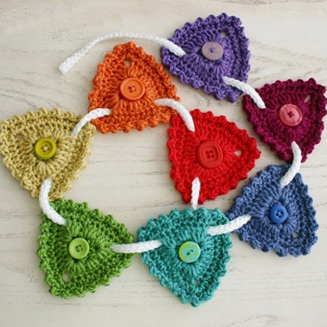 Button Bunting, rainbow triangles and buttons hanging from white cord, free crochet pattern by Susan Carlson of Felted Button | Colorful Crochet Patterns