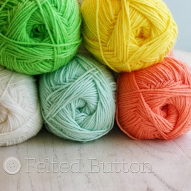 Yellow, orange, green and white yarn stacked on table, Susan Carlson of Felted Button | Colorful Crochet Patterns