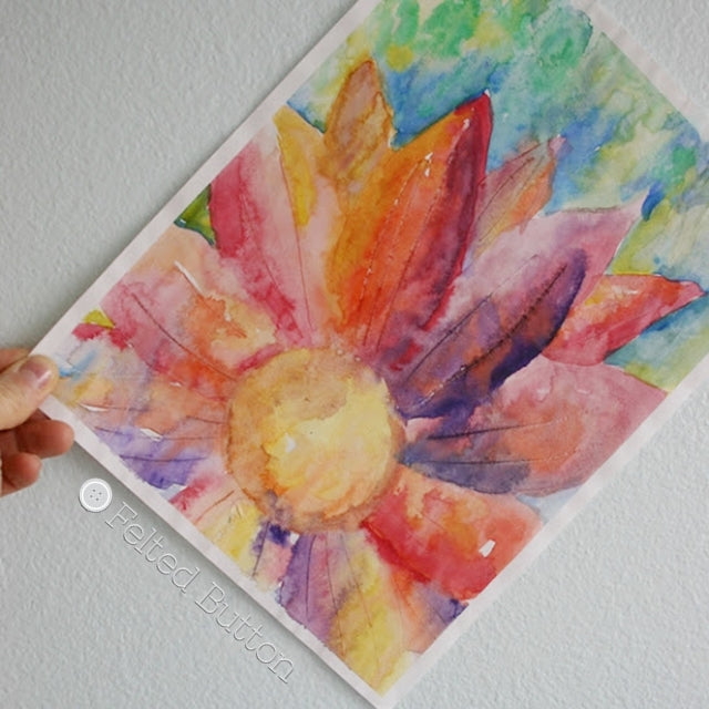Rainbow watercolor painting of large flower against blue sky, by Susan Carlson of Felted Button | Colorful Crochet Patterns