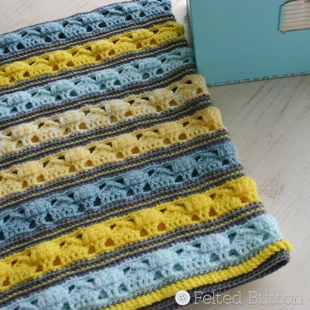 Coming Home Blanket in pastel blues and yellows with little houses and trees on imaginary street, crochet pattern by Susan Carlson of Felted Button | Colorful Crochet Patterns