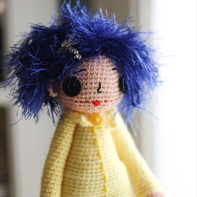 Coraline crochet doll with blue hair and yellow jacket, crochet designed by Susan Carlson of Felted Button | Colorful Crochet Patterns