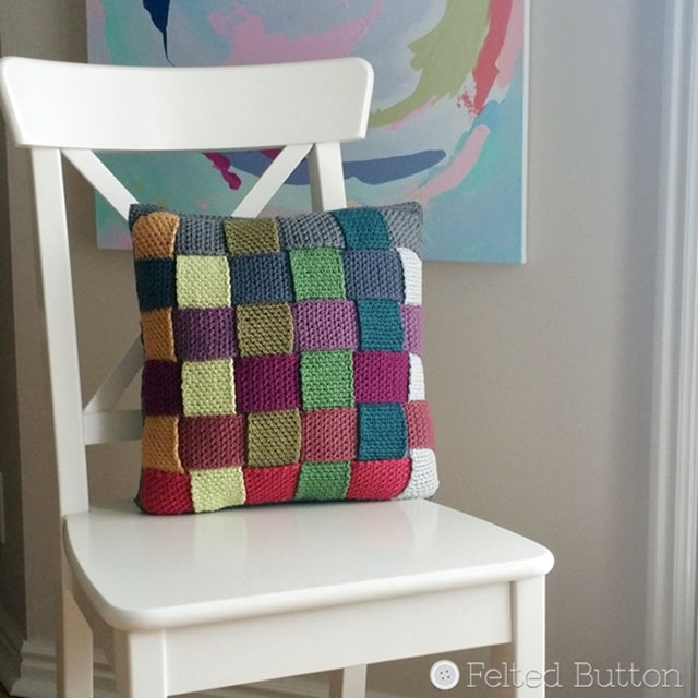Crisscross Catona Cushion Cover, free crochet pattern; woven multi-colored pillow cover made in cotton, resting on white chair, by Susan Carlson | Felted Button | Colorful Crochet Patterns