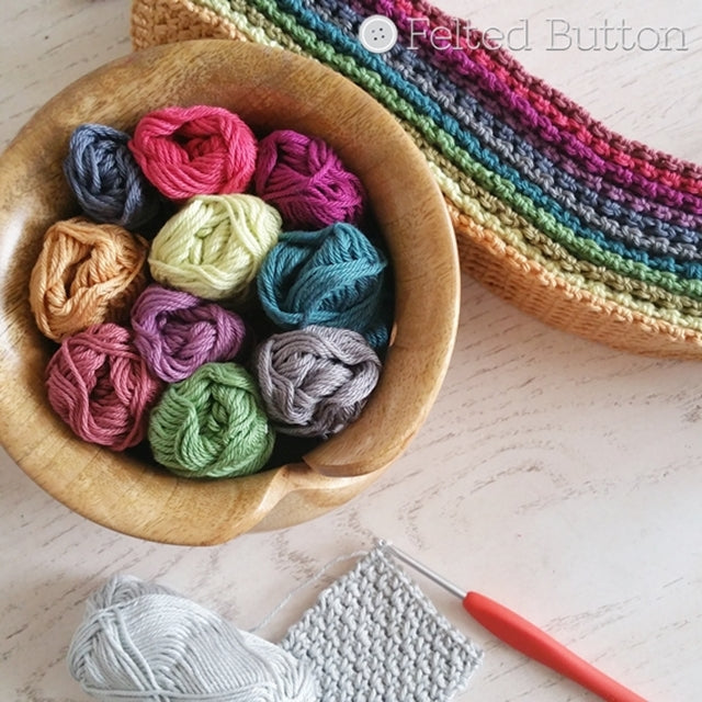 Scheepjes Catona cotton yarn in yarn bowl with jewel-toned colors and crochet hook for Crisscross Cushion Cover crochet pattern by Susan Carlson | Felted Button | Colorful Crochet Patterns