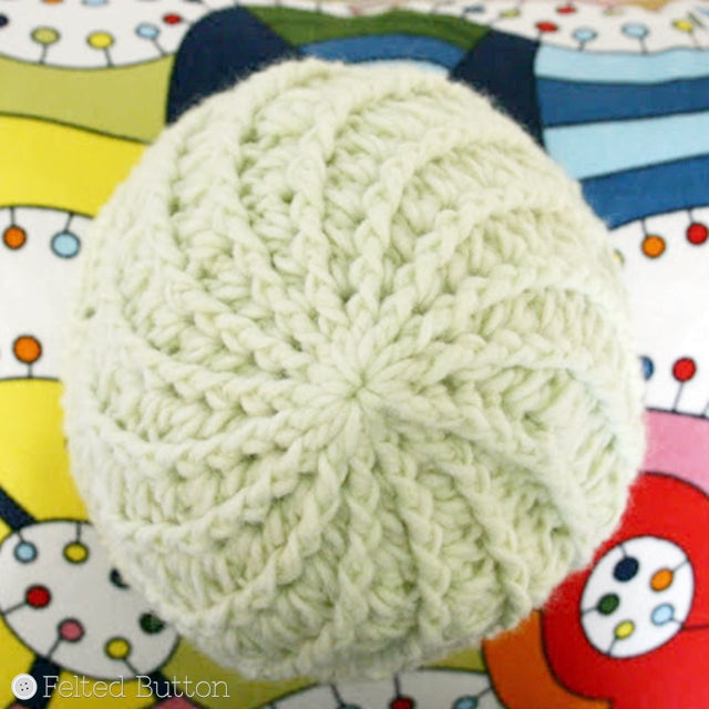 Top view of Divine Hat with swirl and soft green yarn against colorful rainbow background, Susan Carlson of Felted Button | Colorful Crochet Patterns