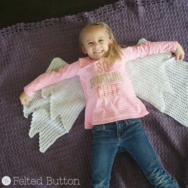 Cute little girl in pink shirt lying on purple blanket with white angel wings, smiling, Embraced By Angels Blanket crochet pattern by Susan Carlson | Felted Button | Colorful Crochet Patterns