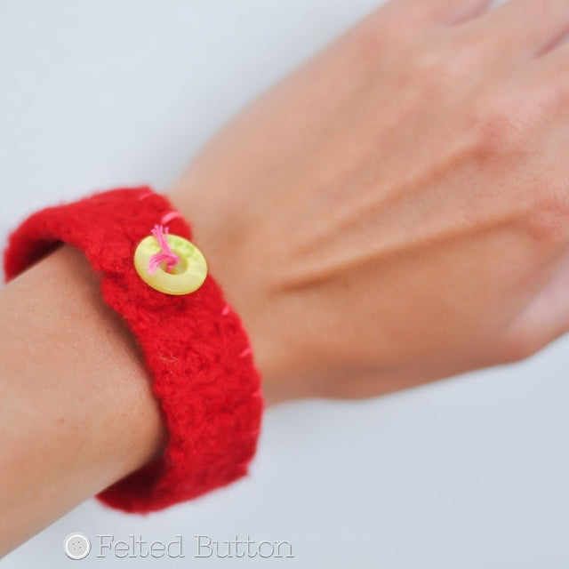 red felted bracelet cuff on wrist with green button and embroidery, Felted Button Bracelet free crochet pattern by Susan Carlson of Felted Button | Colorful Crochet Patterns