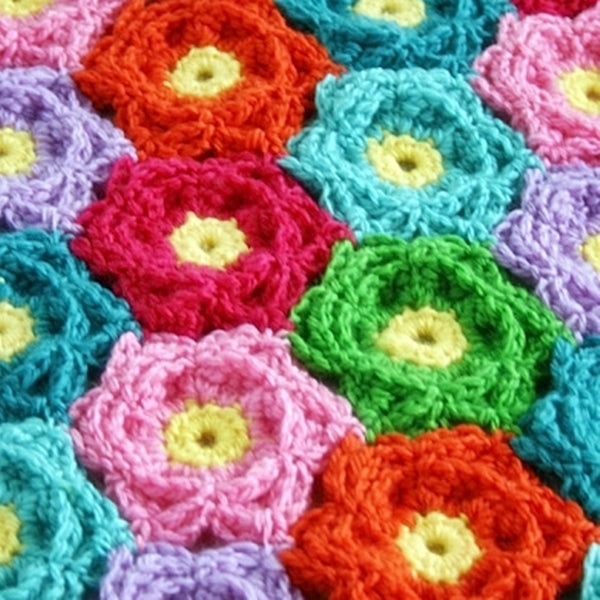 Highly textured crochet flowers in rainbow colors with yellow centers, Waikiki Wildflower Blanket crochet afghan or throw pattern by Susan Carlson of Felted Button | Colorful Crochet Patterns