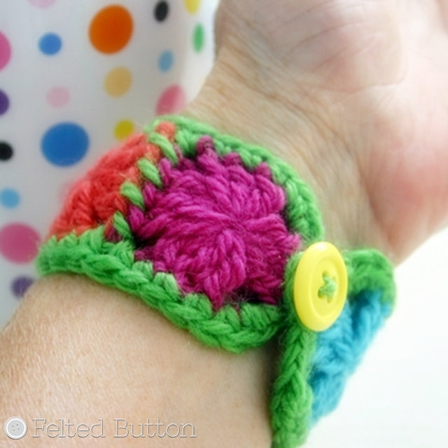 Small colorful single round granny square bracelet in rainbow with yellow button, free crochet pattern by Susan Carlson of Felted Button | Colorful Crochet Patterns, Granny Cuff