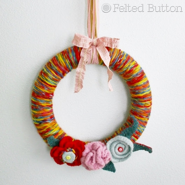 Wreath covered in rainbow yarn hanging by ribbon with felted flowers and buttons, Susan Carlson of Felted Button | Colorful Crochet Patterns