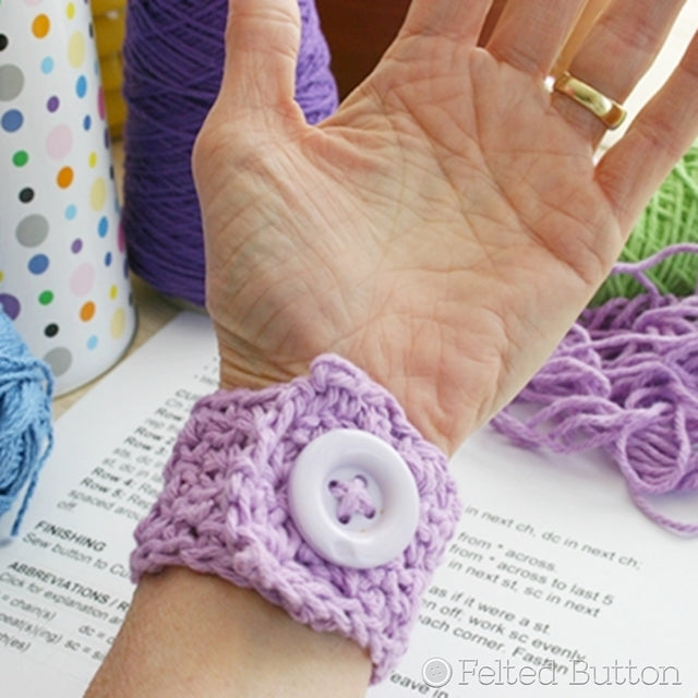 Purple crochet cuff with large lavender button, easy beginner crochet project by Susan Carlson of Felted Button | Colorful Crochet Patterns