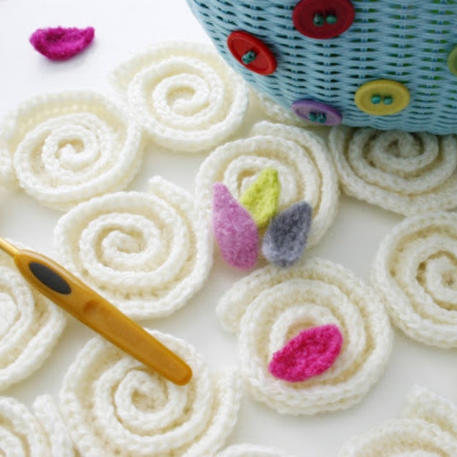 White crochet swirls with felted colorful flowers, Susan Carlson of Felted Button | Colorful Crochet Patterns