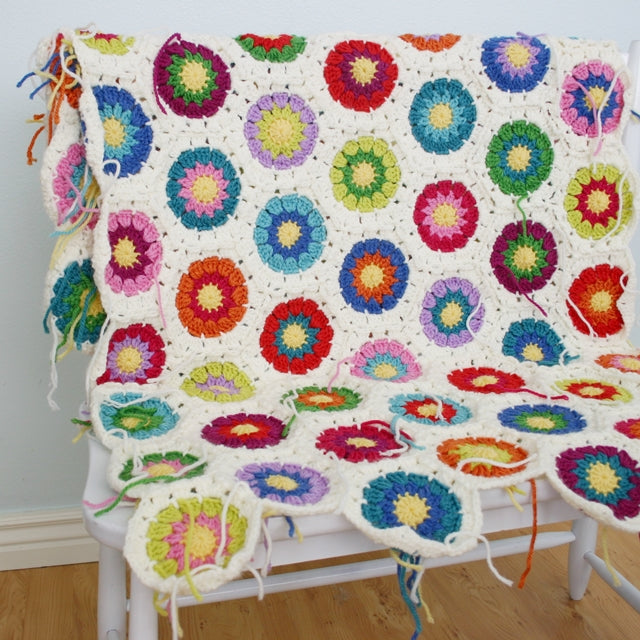 Colorful crochet blanket, hexagons with rainbow centers and white borders, unfinished wip by Susan Carlson of Felted Button | Colorful Crochet Patterns