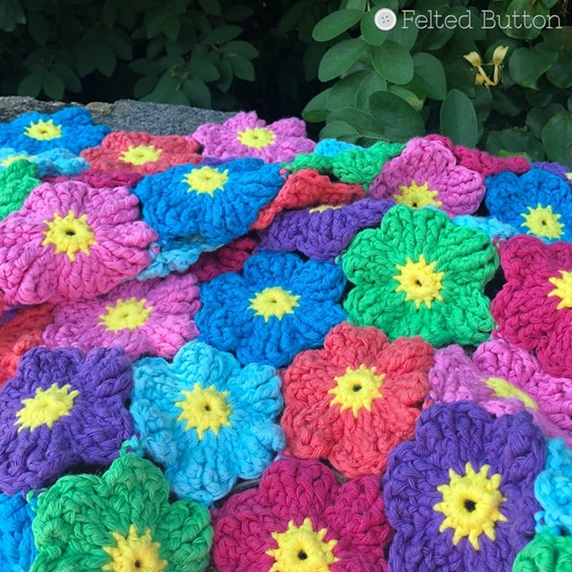 Rainbow if brightly colored crochet flowers blanket with yellow centers, Waikiki Wildflower Blanket crochet pattern made with Scheepjes Cahlista, by Susan Carlson of Felted Button colorful crochet patterns