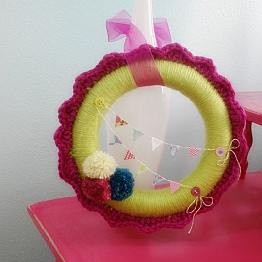 Yarn wrapped wreath in yellow-green and pink with ribbons, pom poms and bunting, by Susan Carlson of Felted Button | Colorful Crochet Patterns