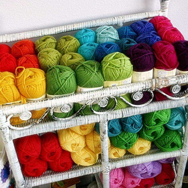 Rainbow of colorful yarn in wicker shelf, Susan Carlson of Felted Button | Colorful Crochet Patterns