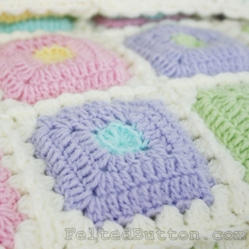 Pastel baby crochet padded quilt in purple, pink, green, blue and yellow, Puffy Patch Blanket crochet pattern by Susan Carlson of Felted Button