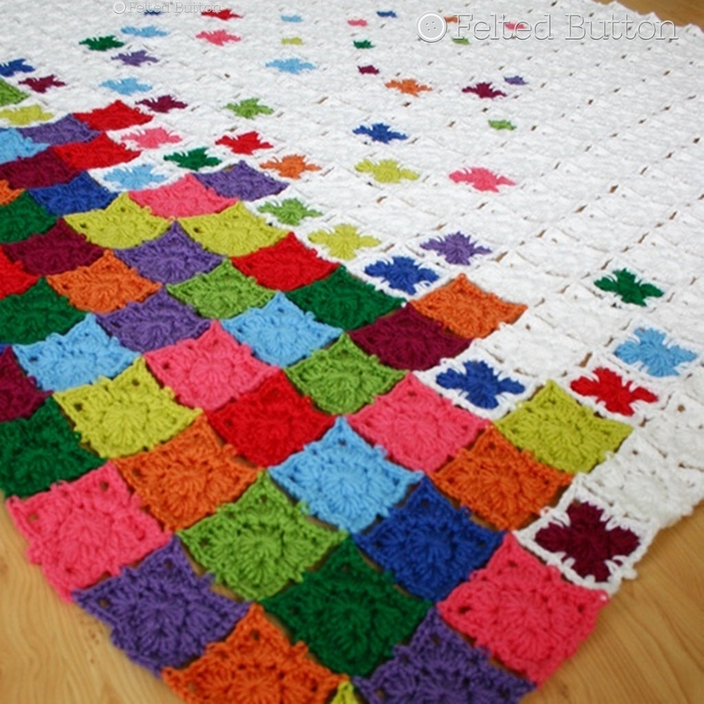 Modern graphic granny square blanket with rainbow colors in pile at bottom, Rainbow Sprinkles Blanket crochet throw pattern by Susan Carlson of Felted Button