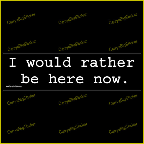 Bumper sticker or magnetic bumper sticker says, I would rather be here now. White lettering on a black background.