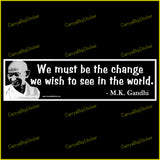 Bumper Sticker or Magnetic Bumper Sticker says, We Must be the change we wish to see in the world. Quote is credited to M.K. Gandhi. White lettering on black background with photo of Gandhi.