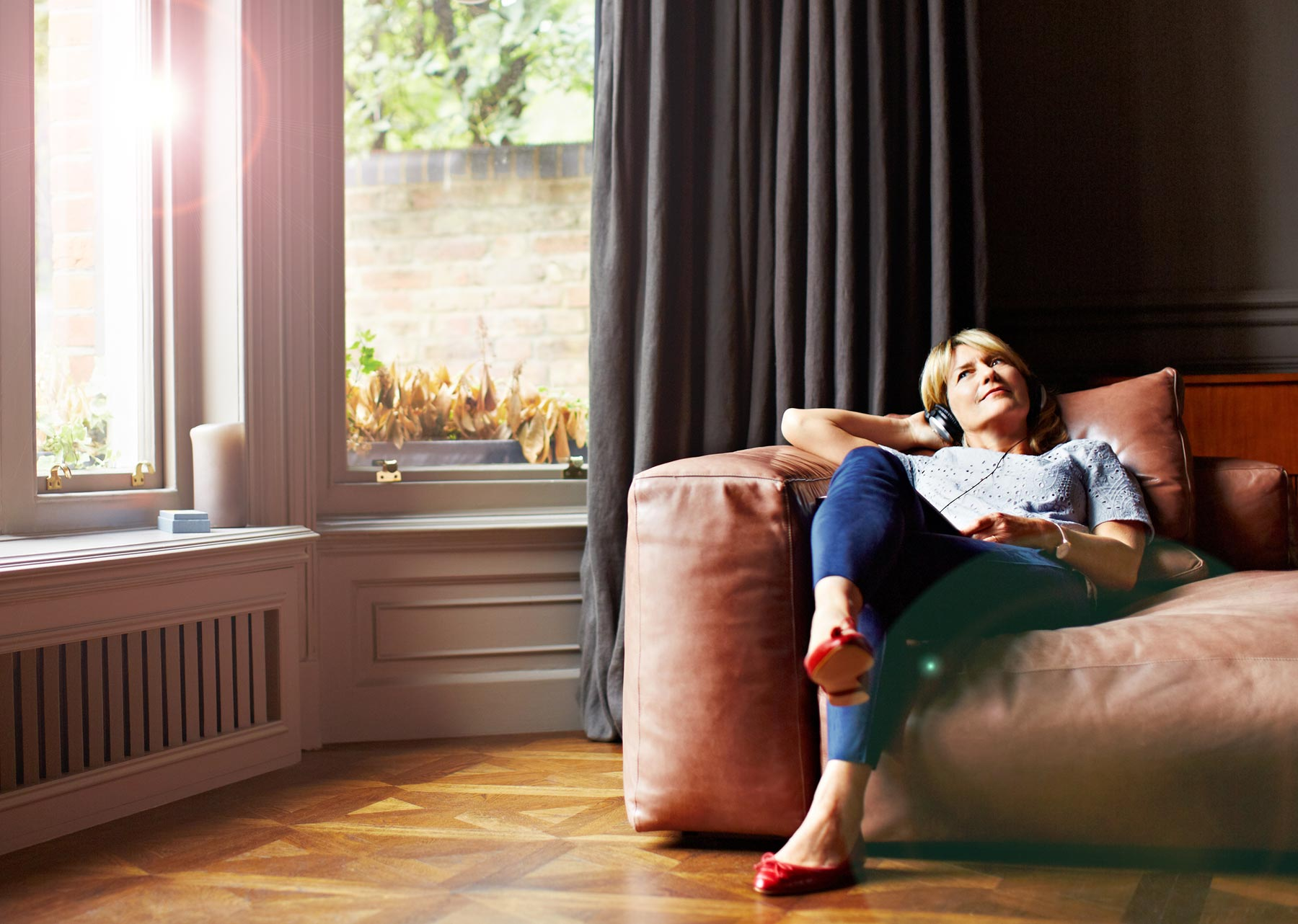 Woman lounging on comfy sofa listening to music in headphones