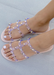 Aurora Clear Jelly sandal with nude sole that has  Gold Studs on all straps and is a slip on sandal.  Sandal has three equally separated horizontal straps that goes all the way to top of the bridge of the foot and one strap in the middle connecting all straps