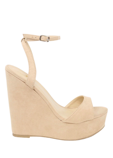 Nude suede ALYSSA wedge with crisscross strap that crosses in the back as the buckle buckles in the side that is silver. Thick to thin back to thick strap in the front.