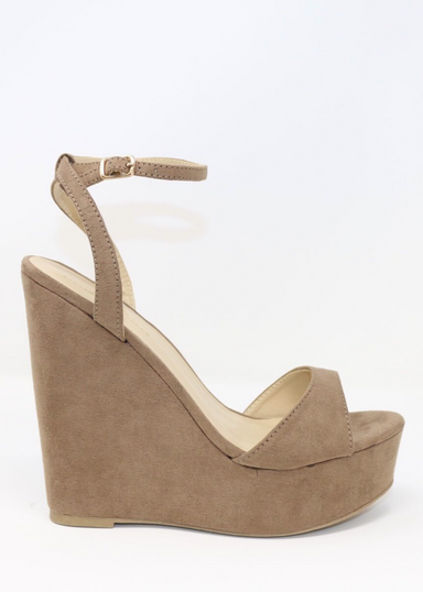 Taupe suede ALYSSA wedge with crisscross strap that crosses in the back as the buckle buckles in the side that is silver. Thick to thin back to thick strap in the front. side view as model is standing