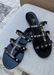 Aurora Black Jelly sandal that has  Gold Studs on all straps and is a slip on sandal.  Sandal has three equally separated horizontal straps that goes all the way to top of the bridge of the foot and one strap in the middle connecting all straps