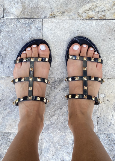 Aurora Black Jelly Studded Sandals.Aurora Black Jelly sandal that has  Gold Studs on all straps and is a slip on sandal.  Sandal has three equally separated horizontal straps that goes all the way to top of the bridge of the foot and one strap in the middle connecting all straps. on the foot