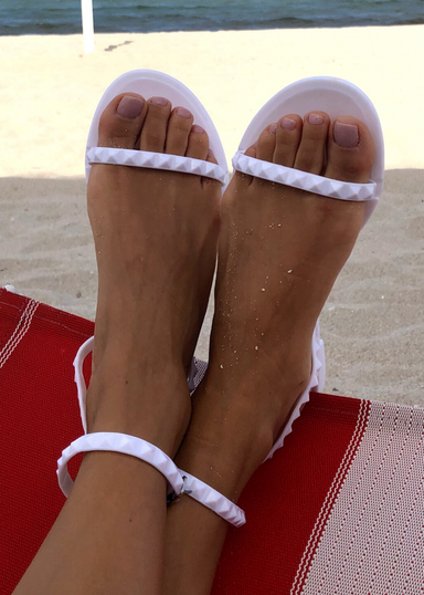 White Aria water proof jelly sandals at the beach on a red beach chair
