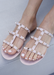 Aurora all  Nude Jelly sandal that has  Gold Studs on all straps and is a slip on sandal.  Sandal has three equally separated horizontal straps that goes all the way to top of the bridge of the foot and one strap in the middle connecting all straps