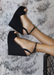 Black suede ALYSSA wedge with crisscross strap that crosses in the back as the buckle buckles in the side that is gold. Thick to thin back to thick strap in the front. Side view as model is on a chair