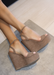 Taupe suede ALYSSA wedge with crisscross strap that crosses in the back as the buckle buckles in the side that is silver. Thick to thin back to thick strap in the front. side view on a grey couch.