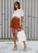 @carlanunez_ styled in a white top and rusted colored shorts accessorized with Amora in nude.