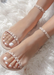 Womens feet propped up on a white fur rug wearing Nude Aris sandals.
