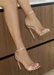 ALI heel in rose gold that is pictured from above on a wood background for better view. Ali Heels in rose gold that has a buckle on the ankle and cover heel in the back as well as thick to thin and thick again for secure and comfort