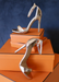 Ali sandal heels in Rose Gold propped up on Orange boxes.