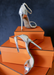 "Silver Metallic ""Ali"" sandal heels propped up on orange boxes."