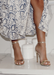 Ali heels in Gold propped up on top of a marbled countertop styled with a white and navy snake print dress.